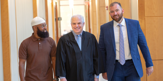From left, Wasim Kabir, a graduate of the Camden Federal Reentry Court program, with U.S. District Judge Noel L. Hillman, an adjunct professor at Rutgers Law School, and Steve Salinger RLAW'15, an attorney and volunteer in the program.
